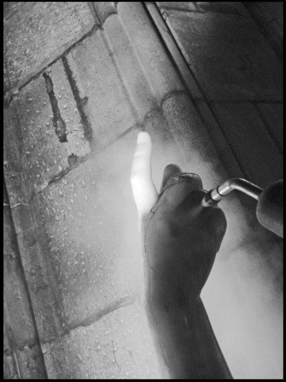 l'image d'accueil est une photographie en noir-et-blanc. Cela montre la main d'une sculpture en marbre que le restaurateur nettoie.
